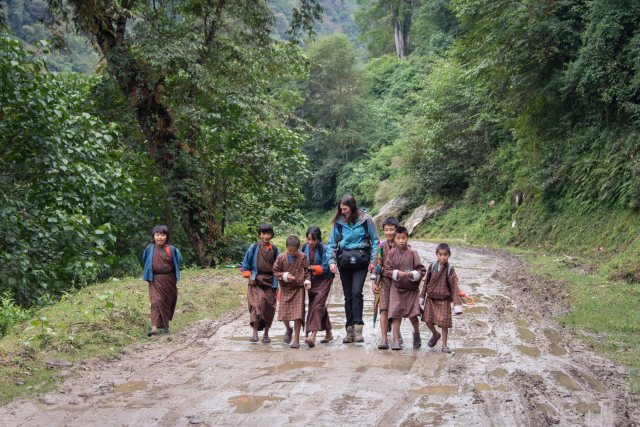 Kids in kiras and ghos walk home from school in Gasa, Bhutan