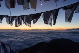 Sunrise above an ocean of clouds and prayer flags in Bhutan
