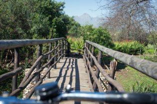 Bike handlebars in front of a small bridge
