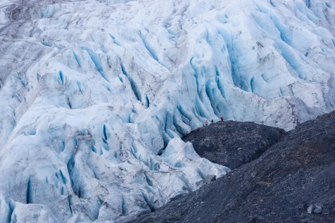 A group of people in the distance stand near the crevasses of Exit Glacier