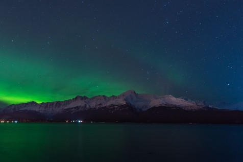 Stars and Aurora Borealis above snow covered mountain peaks and a bay