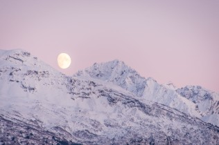 The moon rises above snow covered mountains on the Kenai Peninsula