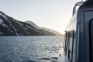The side of a boat near mountains in Alaska
