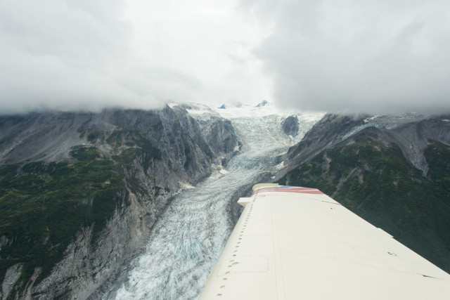 a glacier and mountains with the wing of a plane in view