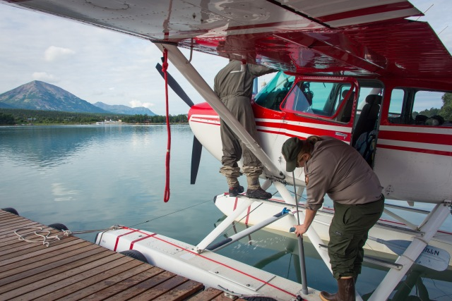 two people ready a float plane for flight on a dock
