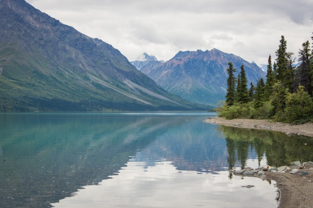 mountains and trees reflect in the blue waters of upper twin lake