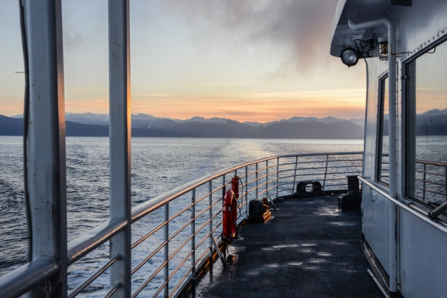 the deck of a fery ship at sunrise with mountains in the distance