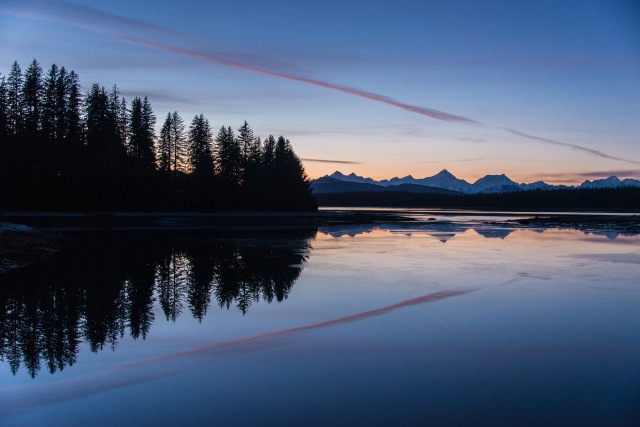 sunset reflected in still waters with trees and mountains